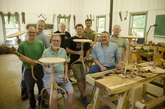 Woodworking students in a woodworking class holding shaker candle stand tables with Moravian workbenches
