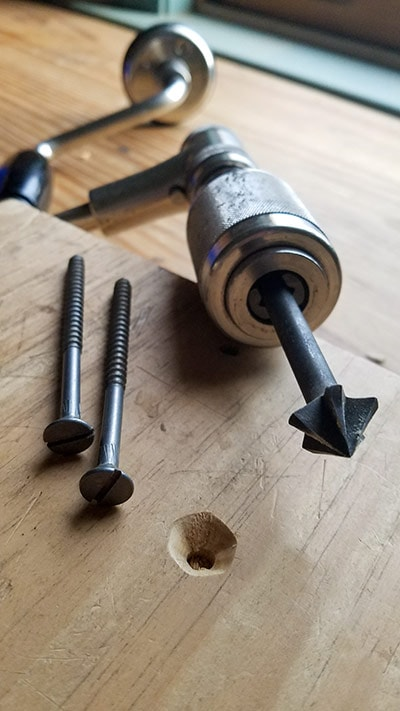 vintage countersink auger bit in a stanley yankee 2101 A hand brace drill with slotted screws nearby