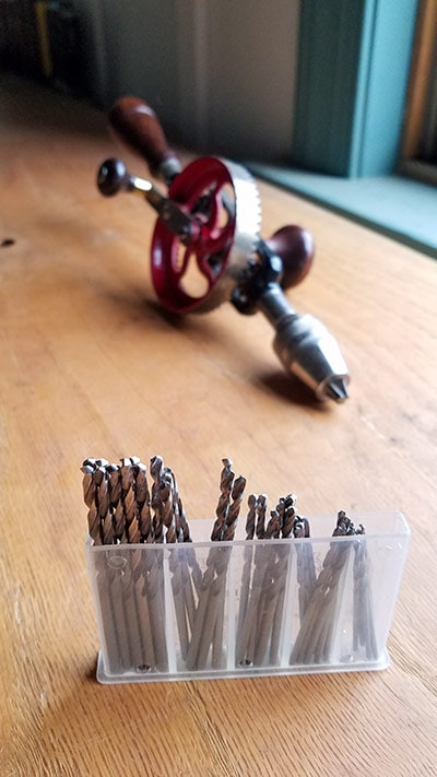 box of new Rockler drill bits with a millers falls No. 5 egg beater hand drill in the background on a woodworking workbench