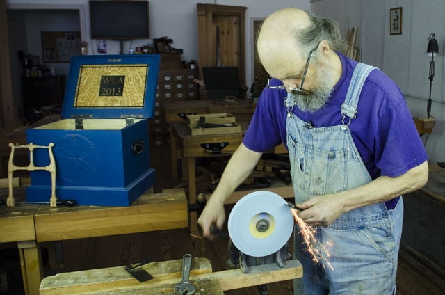 Bill Anderson sharpening a hand plane iron on a hand crank grinder with sparks