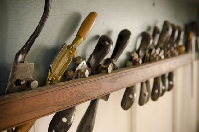 Woodworking spokeshaves lined up on a shelf