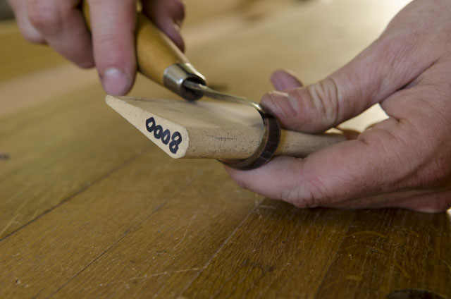 sharpening a hook knife for green woodworking and spoon carving with a small water slip stone that says 8,000 on it