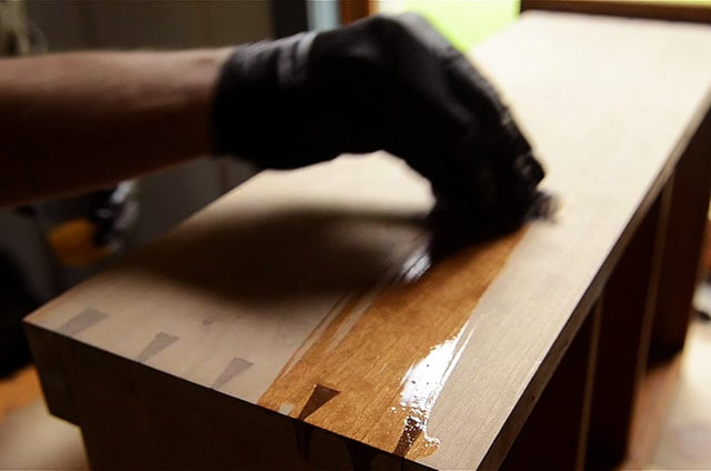 Woodworker applying danish oil to a dovetail cupboard case piece