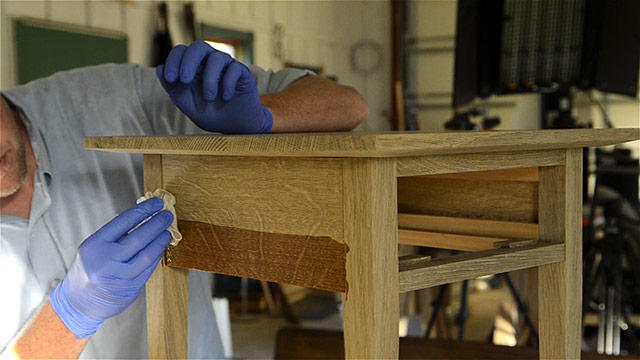 Joshua Farnsworth applying wood finish to an oak table apron with wood figure in his woodworking workshop