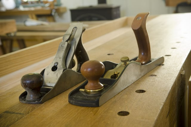 Two hand planes sitting on a woodworking workbench Stanley number 3 smoothing plane and Lie-Nielsen number 62 low angle jack plane