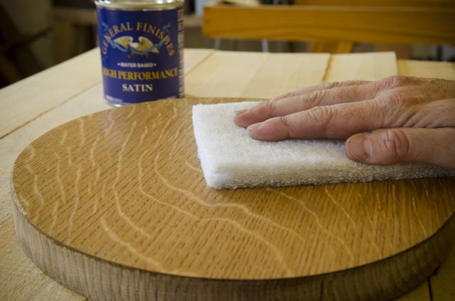 Man's hand scuffing a figured white oak piece of wood with a white 3M Scotch-brite abrasive pad with a can of water based wood finish made by General Finishes