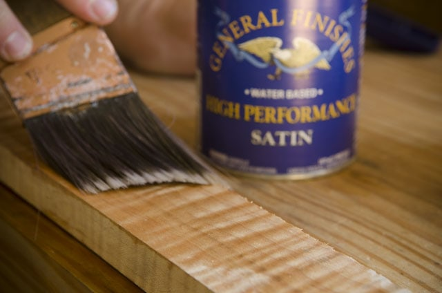 Paint brush applying general finishes water based high performance satin wood finish on figured maple