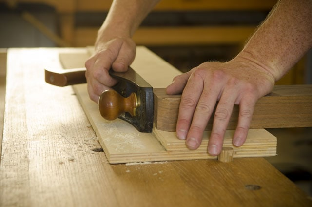 Woodworker using a shooting board with a Lie-Nielsen number 62 low angle blog plane to shoot the end grain of a board on a woodworking workbench