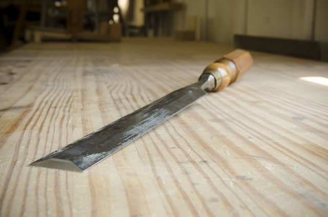 Antique paring chisel for woodworking on a woodworking workbench top