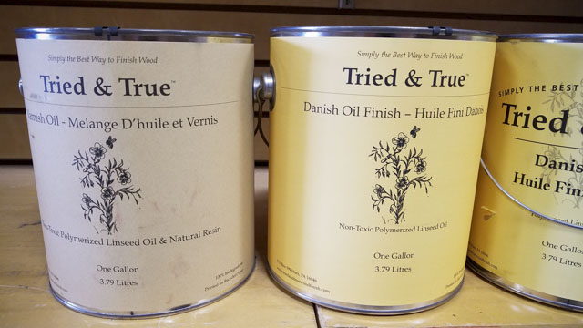 Gallon cans of Tried & True Danish Oil wood finish sitting on a shelf in a woodworking store