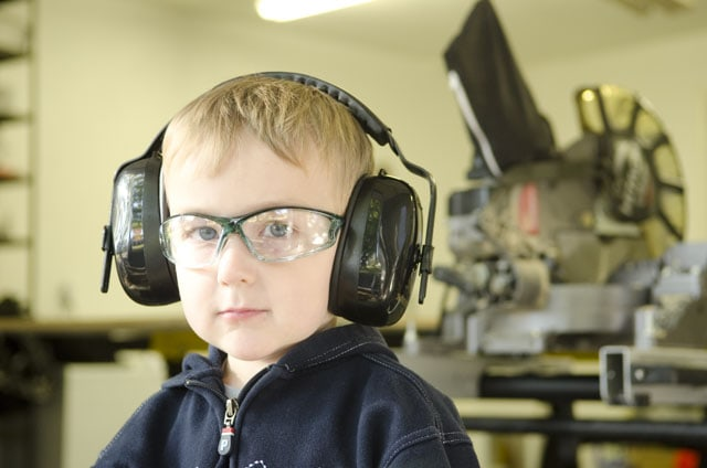 Young boy wearing safety glasses and hearing protection in a woodworking workshop