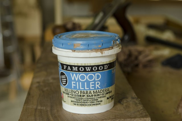 Plastic Container Of Famowood Red Oak Wood Filler With A Handplane In The Background Sitting On A Woodworking Workbench