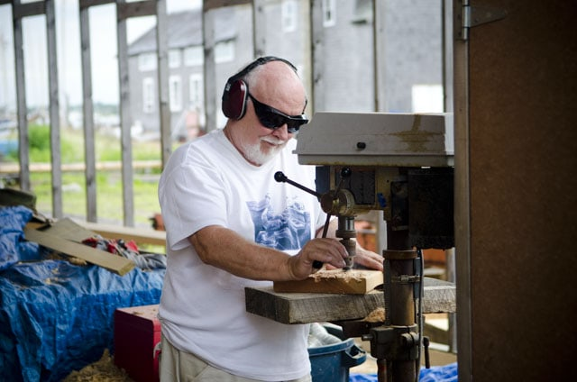 Old man using a drill press in a ship yard in Vineyard Haven Martha's Vineyard