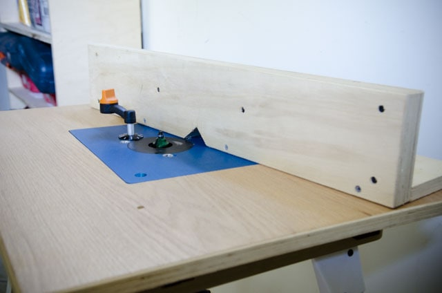 router table with blue insert and wooden fence