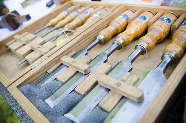 Set of tang bench chisels in a display case at a woodworking tool sale