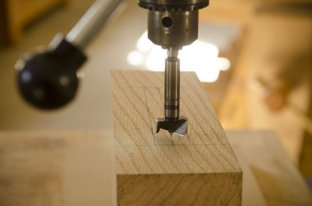 Forstner bit in a drill press ready to bore out a mortise on an oak board