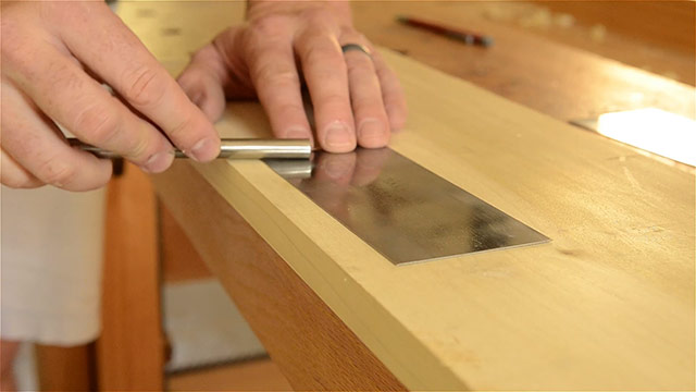 Drawing out a burr on a card scraper with a burnisher