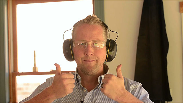 Joshua Farnsworth wearing safety glasses and hearing protection giving a thumbs up