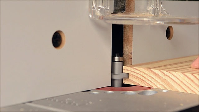 woodworker cutting a groove in a board on a router table for a tongue & groove joint