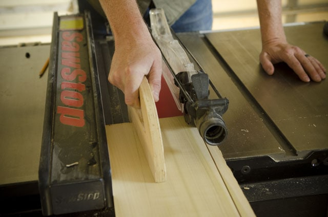 Joshua Farnsworth pushing a poplar board across a SawStop table saw with a wooden push stick