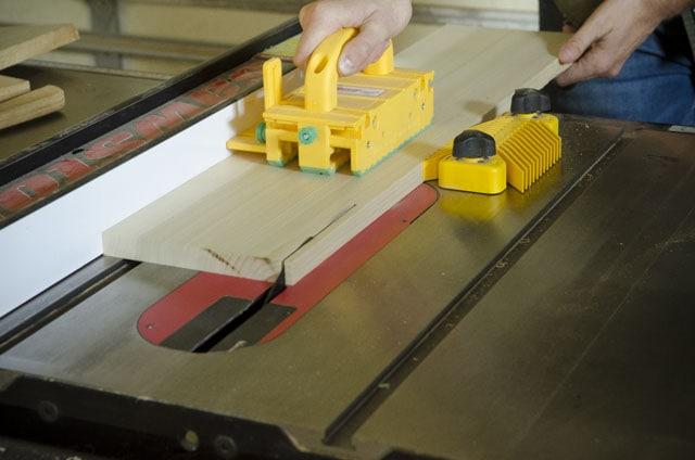 Joshua Farnsworth pushing a poplar board across a SawStop table saw with a yellow GRR-RIPPER table saw pushblock
