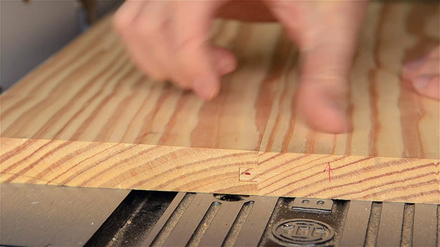 woodworker displaying a tongue & groove joint on a router table top