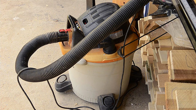 Shop vac vacuum hooked up to a router table with lumber in the backgorund
