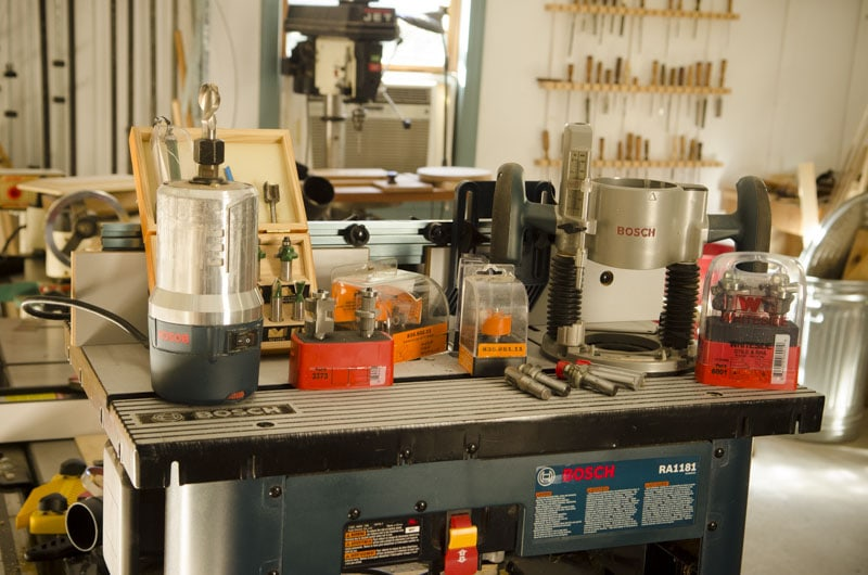 A Bosch Router Table With A Bunch Of Router Accessories, Including A Router, Base, And A Lot Of Router Bits