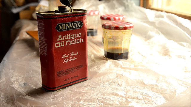 Jar of Minwax antique oil finish with jars of aniline dye in the background