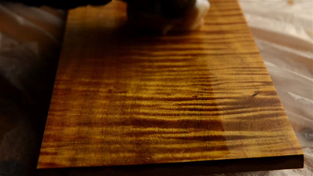 Wiping Minwax antique oil finish on a curly maple board