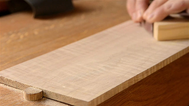 Sanding curly figured maple board on a woodworking workbench