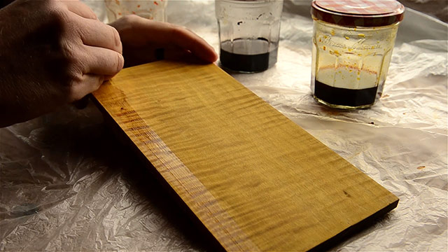 Wiping boiled linseed oil onto a curly maple board that has been colored with aniline dyes