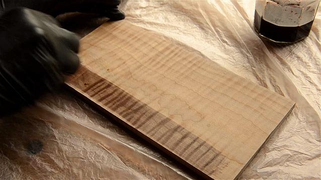 Wiping dark walnut aniline dye onto a curly maple board