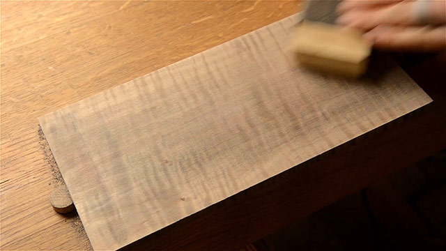 Sanding the dark walnut aniline dye coloring off of a curly maple board