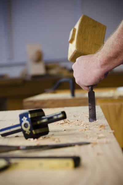 Woodworker using a chisel and joiner's mallet to make a Portable Moravian workbench