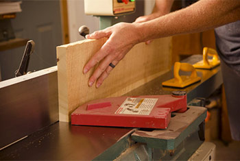 Joshua Farnsworth jointing the edge of a board on a Grizzly power jointer