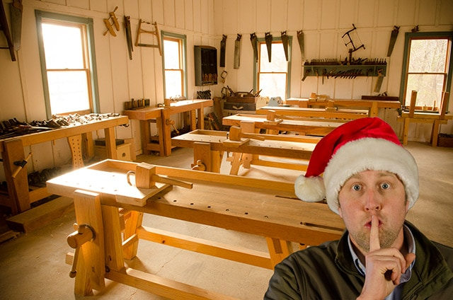 Joshua Farnsworth in a Santa Christmas hat with his finger up to his mouth shhh with the woodworking school in the background