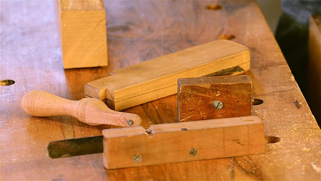 David Ray Pine displaying multiple scratch stocks on a woodworking workbench