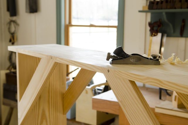 Shaker bench sitting on a workbench with a Stanley block plane for woodworking plans