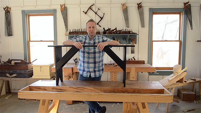Joshua Farnsworth standing in his woodworking workshop over a shaker bench