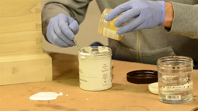 Mixing yellow paint pigment into powdered milk paint in a plastic container