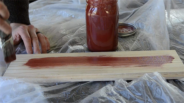 Testing homemade milk paint from scratch by painting it on a scrap board of pine with jar of red milk paint