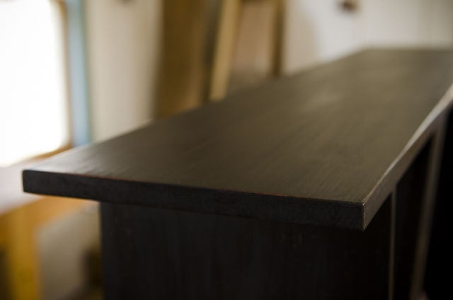 Shaker bench with black milk paint with red undercoat in home made milk paint tutorial