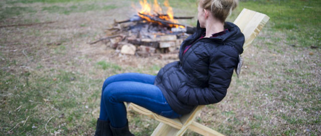 Beautiful Blond Woman Sitting On A Viking Camp Chair With A Camp Fire In The Background