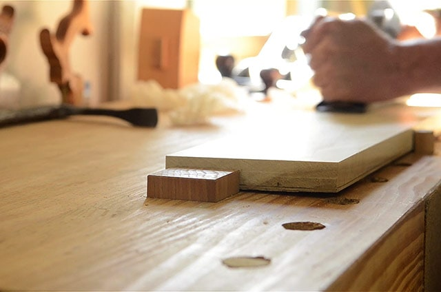 Workbench planing stop mortised into workbench top with handplane in background