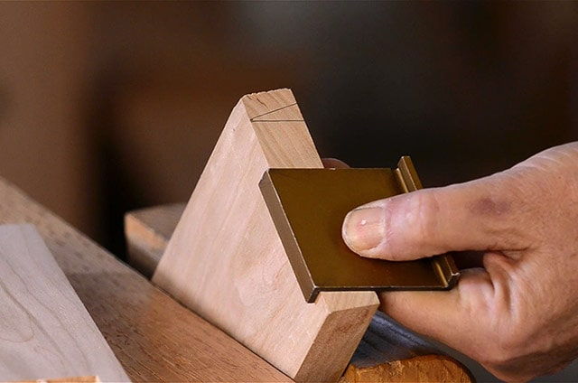 Dovetail marker on the end of a cherry board for woodworking