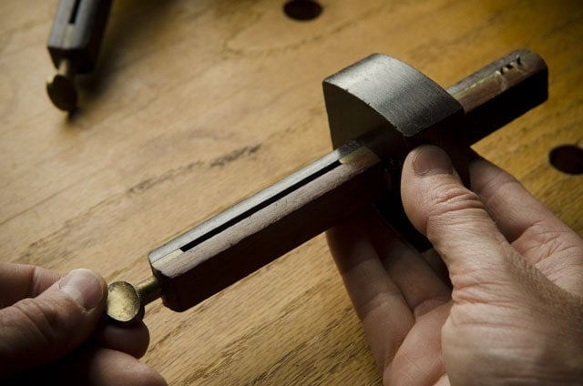 Antique wooden marking gauge held over a Roubo woodworking workbench with other marking gauges in the background