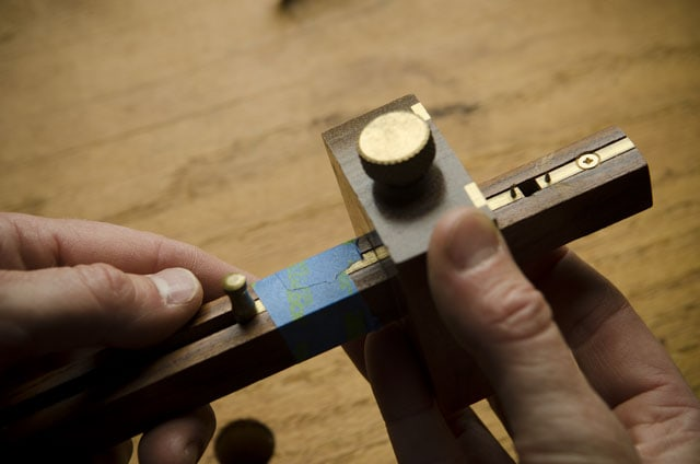 Crown mortise gauge with blue painter's tape over a Roubo woodworking workbench