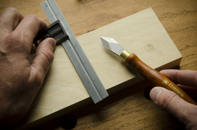 Narex marking knife after cutting a knife line on a board with a double square for woodworking