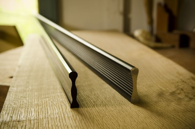 metal straight edges sitting on a roubo woodworking workbench